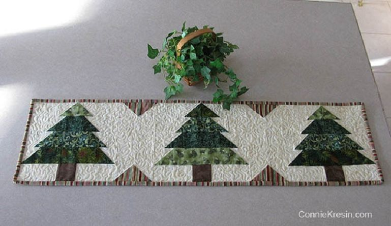 White Table runner with green Christmas trees patterns on it