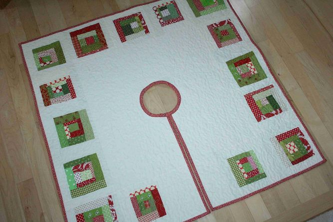 White log cabin Christmas tree skirt with green and white decorations