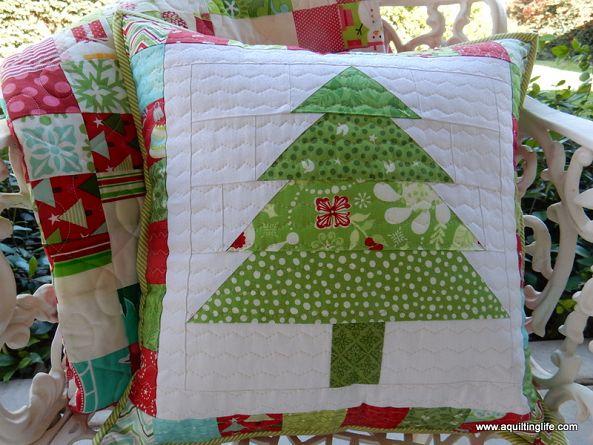 White throw pillow with green christmas tree sewn on it