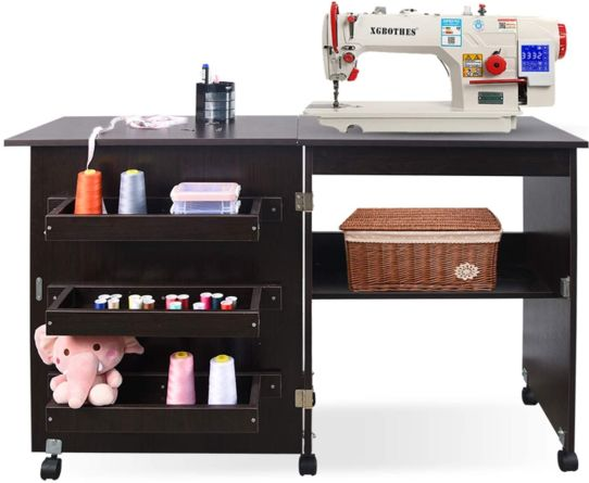 Black foldable sewing cabinet with a white sewing machine on it
