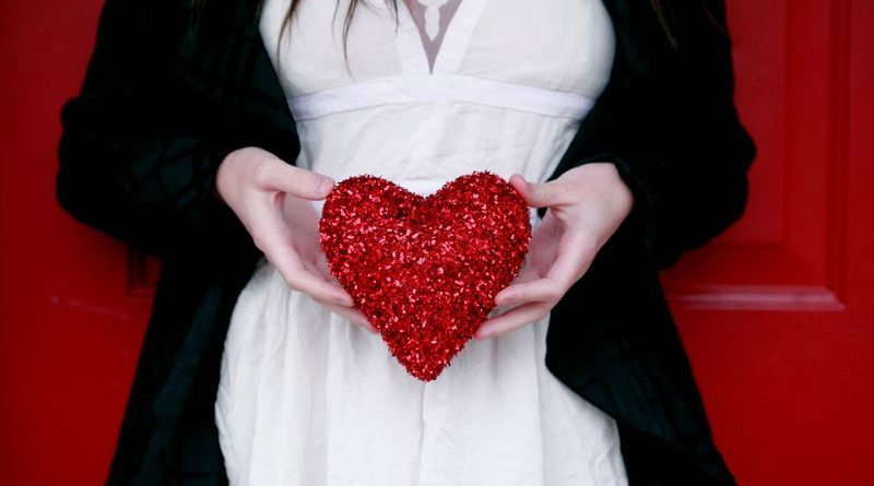 Good Example of a lovely Valentine sewing project- woman holding a red heart sewn from glittering material