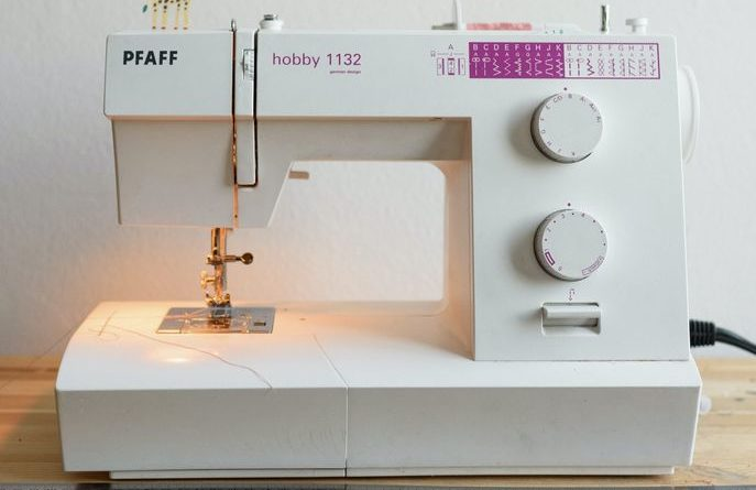 white Pfaff sewing machine on a brown table with sewing light on