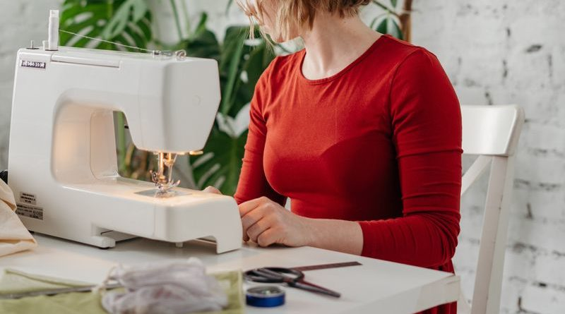 woman in red sewing on a white sewing cabinet with a white sewing machine