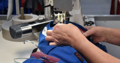 Woman's hands sewing a blue trouser on a sewing machine
