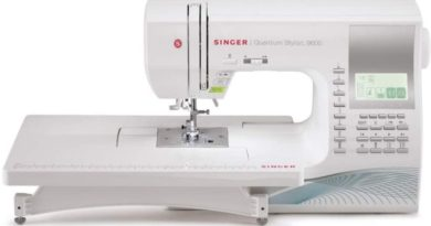 white portable sewing machine, by Singer