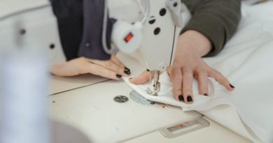 woman doing some sewing machine stitches on white cloth