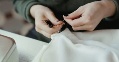 woman hand sewing some stitches on a white dress