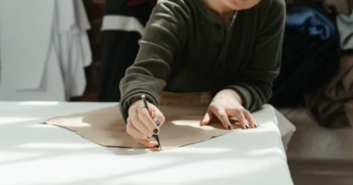 Woman measuring a sewing pattern on a table