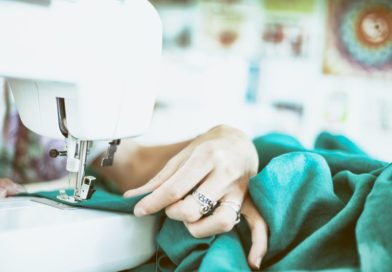 woman sewing green cloth on a white sewing machine