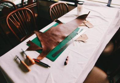 cutting mat for quilting and sewing, with leather on it, on a white sewing table with fabric and cutting accessories